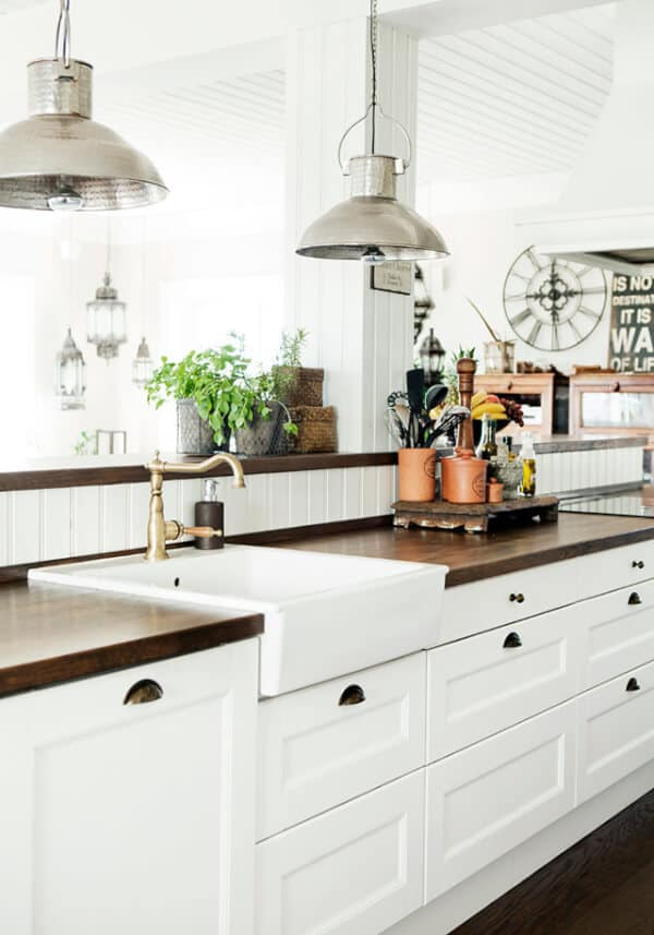 I like the simple white cabinets with the black handles, the industrial lights and the apron sink in this kitchen.